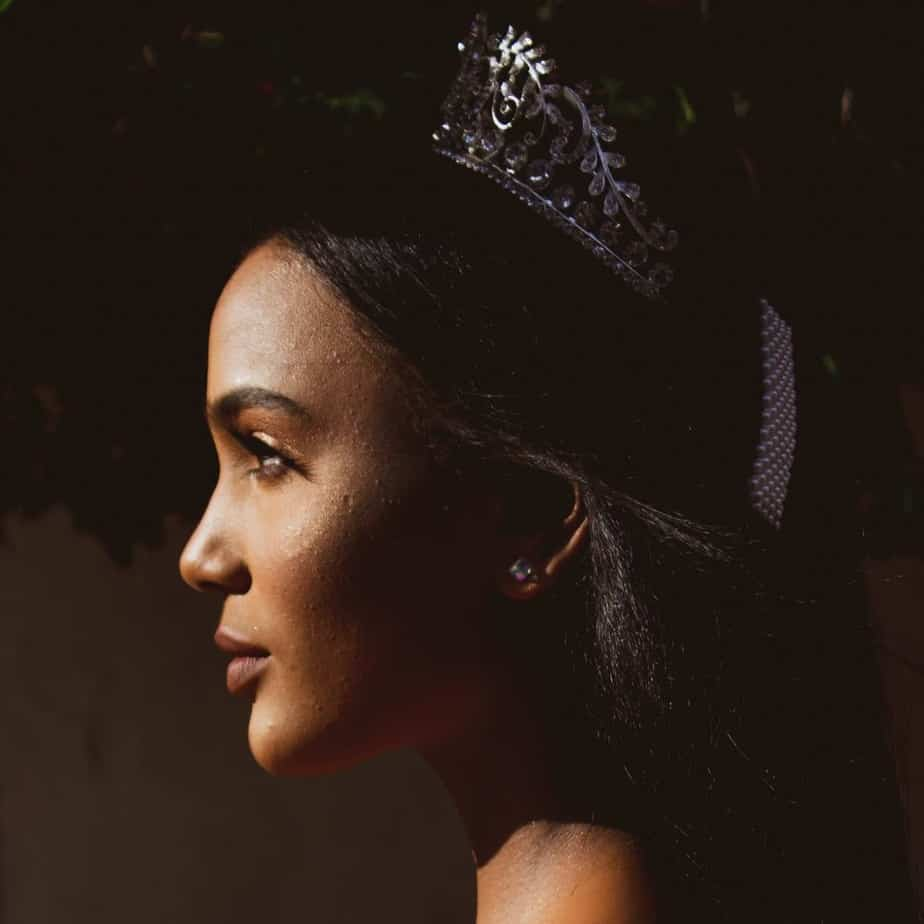 An image of a woman's profile with a crown on her head and a dark background