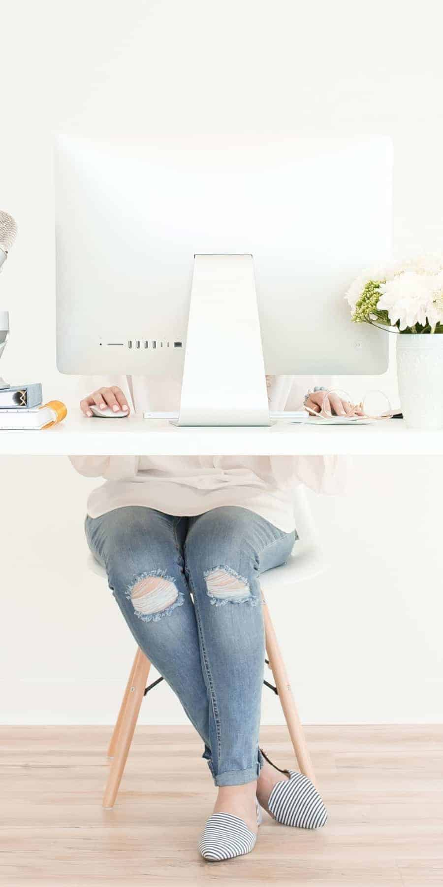 An image of a woman in jeans sitting at a desk in front of a white Mac monitor which is hiding her upper body and flowers on the desk and she is sitting with ankles crossed on a wooden chair on a hard wood floor