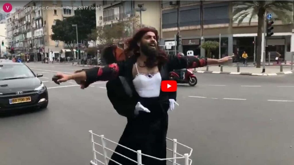 an image of a man in Israel on Purim dressed as Rose from the Titanic with a fake Jack behind him riding on a motorized scooter that looks like the ship - goes to the YouTube video