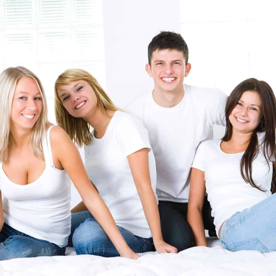 3 girls and a boy all in white t-shirts sitting on a rug close together smiling
