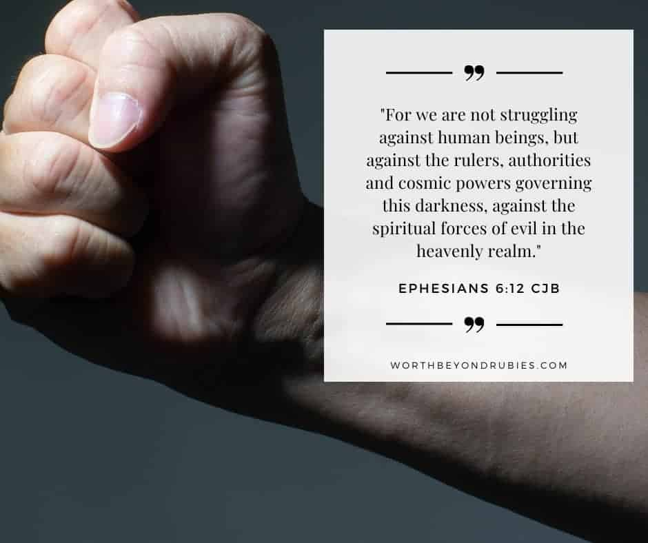 Male clenched fist on grunge background  with Ephesians 6:12 quoted in the Complete Jewish Bible version - Holy and Blameless