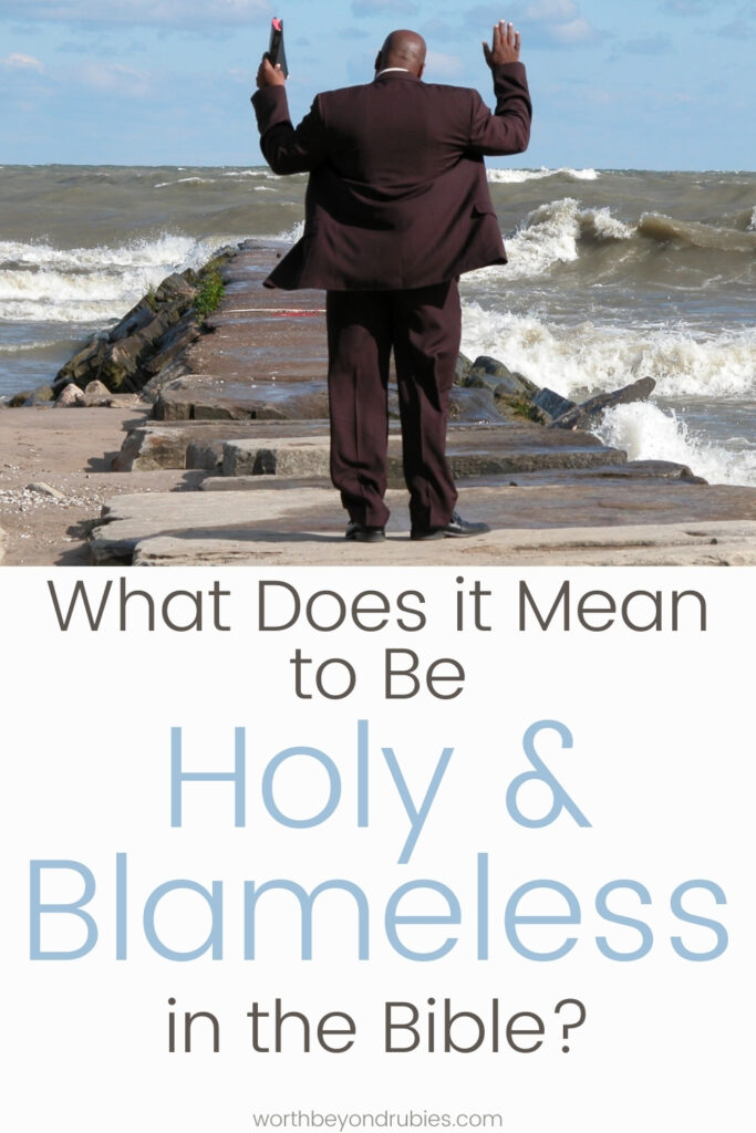 A man in a suit on a pier at the beach with a Bible and his hands up in praise with text that says What Does it Mean to Be Holy and Blameless in the Bible?