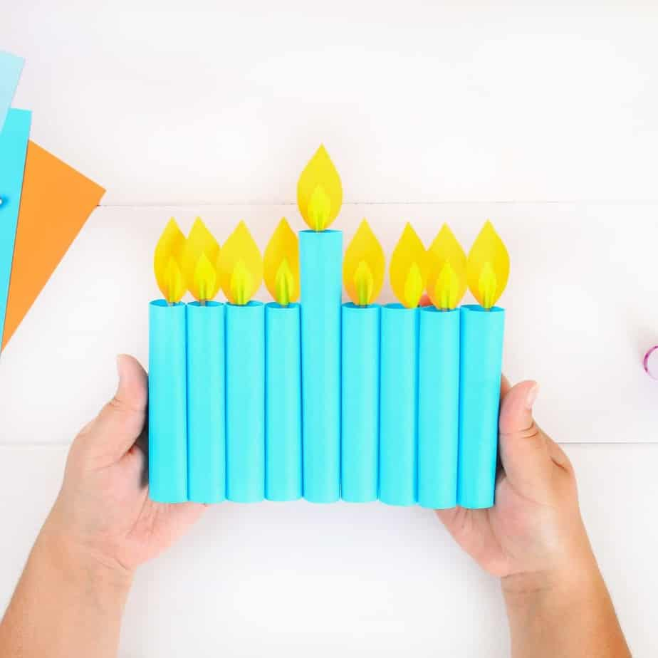 An image of someone's hands holding a paper menorah with blue paper candle flames in yellow