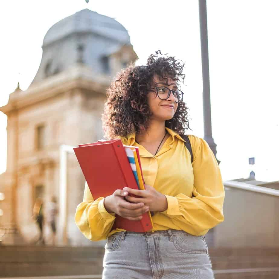 A young black woman holding books outside a college building - Homeschooling Silo Page
