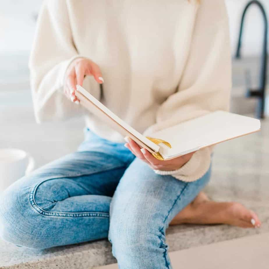 An image of a woman from the shoulders down, in a beige sweater and jeans, sitting on the floor with a notebook open in her hands