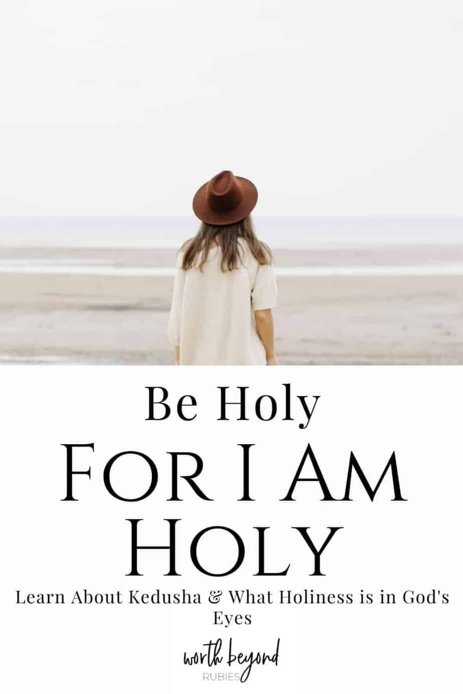 A woman with long brown hair in a beige sweater and a brown hat standing on a beach facing the water and text that says Be Holy for I am Holy - Learn About Kedusha and What Holiness is in God's Eyes