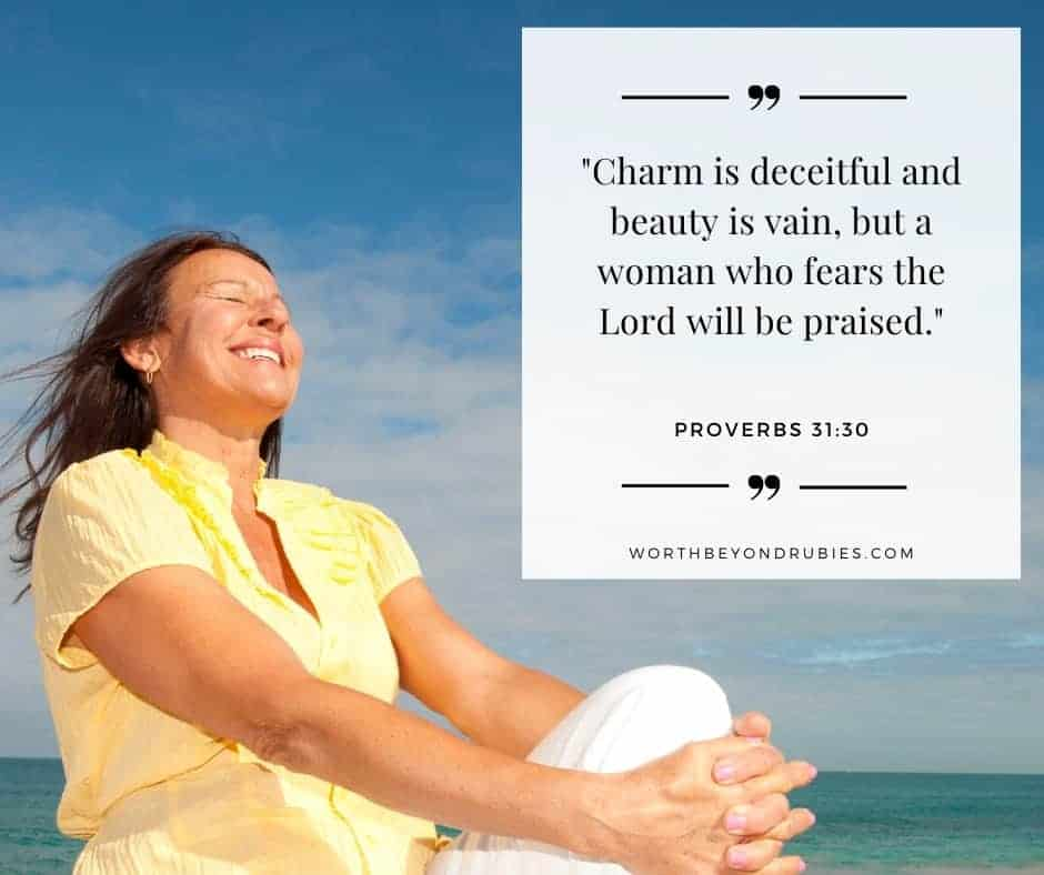 a woman sitting at the ocean smiling and Proverbs 31:30 quoted