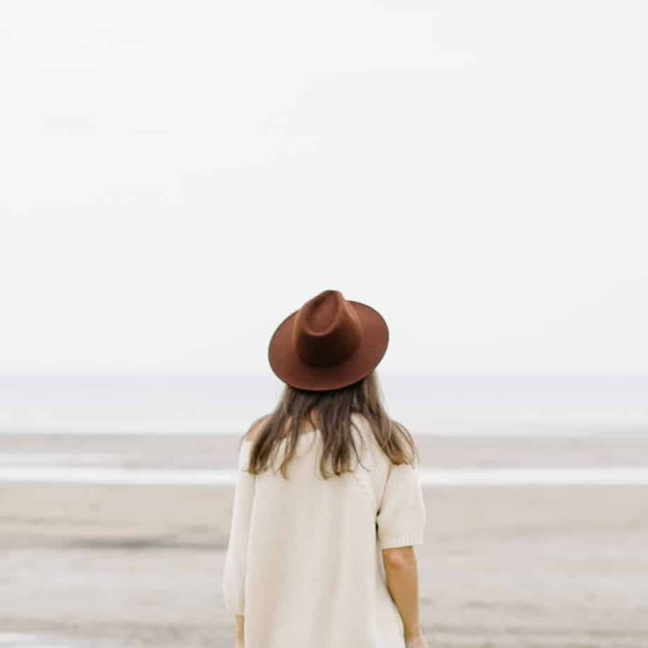 A woman with long brown hair in a beige sweater and a brown hat standing on a beach facing the water