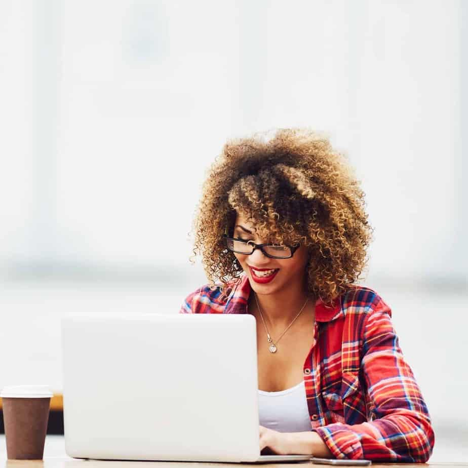 An image of a woman of color with curly hair and glasses in a red flannel shirt sitting at a laptop smiling