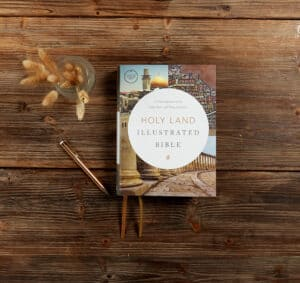 an image of the Holy Land Illustrated Bible on a wooden table with what looks like wheat next to it