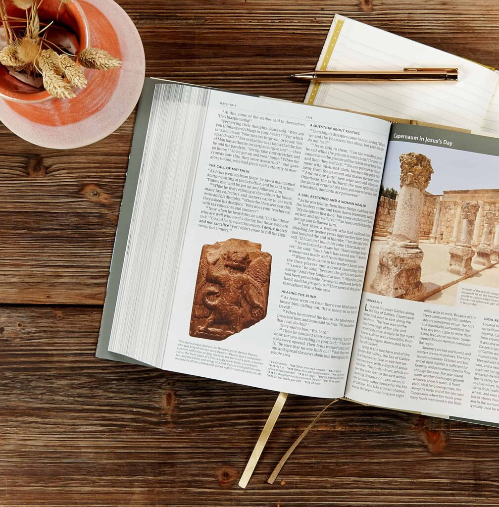 An image of the Holy Land Illustrated Bible, opened to a page on a wooden table with a plant next to it