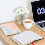 a Bible on a desk next to a laptop and a cup of tea for post called How to Read the Bible Daily and Stay Consistent