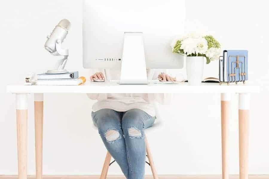 A woman sitting behind a mac computer on a desk