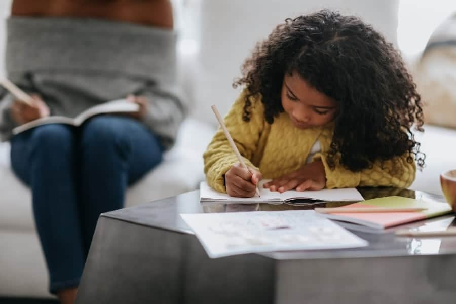 A little girl doing schoolwork at a coffee table with her mother in the background