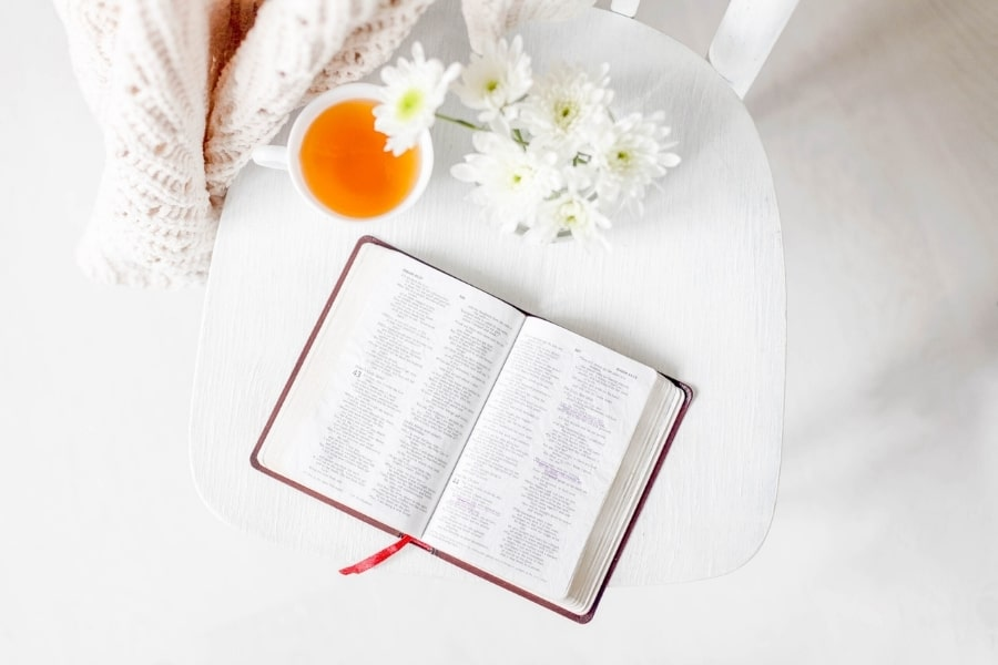 A bible open next to a cup of tea and some flowers